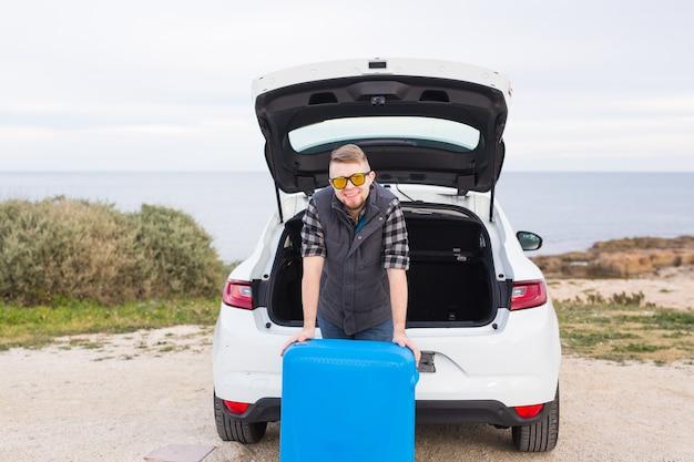 車の後ろに立って笑顔で行く準備をしている男。車の開いたトランクの近くに立っている若い笑い男。