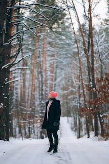 눈으로 둘러싸인 숲 한가운데 도로에 서있는 사람