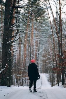雪に囲まれた森の真ん中の道に立つ男