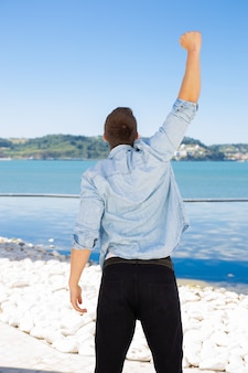 Guy standing at sea and celebrating success