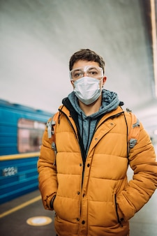 Guy standing at station in medical protective mask on his face