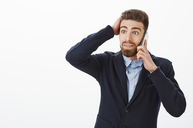 Ragazzo in piedi sbalordito riceve un'offerta fantastica. ritratto di imprenditore maschio caucasico senza parole sorpreso e contento in elegante abito formale toccando taglio di capelli parlando tramite cellulare stupito
