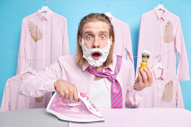 男は目をそらし、口を開いたまま、アイロンをかけて髭を剃ろうとすると同時に、フォームジェルを顔に塗って、急いでいる青のポーズをとっている