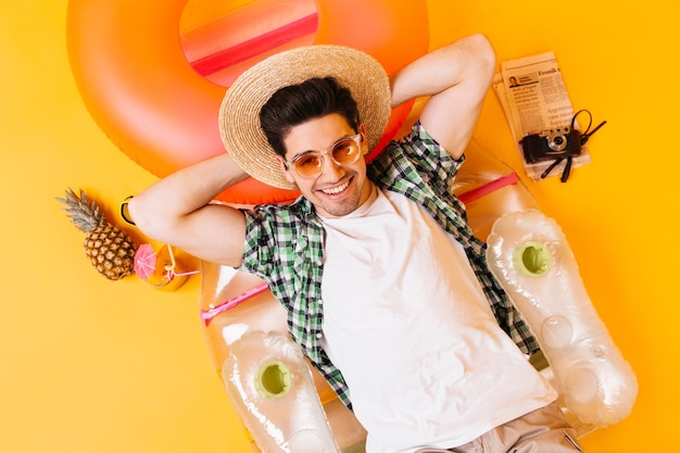 Guy in straw hat, glasses and white t-shirt is resting on inflatable mattress with pineapple cocktail and retro camera.