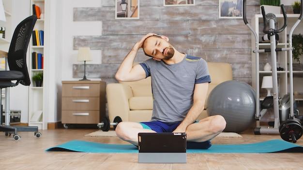 태블릿 컴퓨터에서 온라인 피트니스 수업을 보고 목 근육을 스트레칭하는 남자.