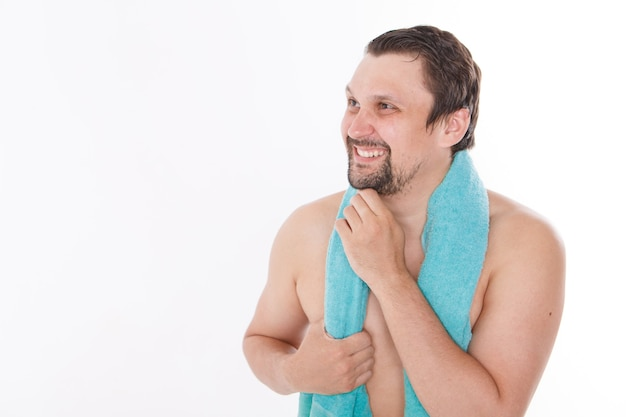 The guy strokes his beard. morning treatments in the bathroom. blue towel around her neck. isolated on a white background. copy space