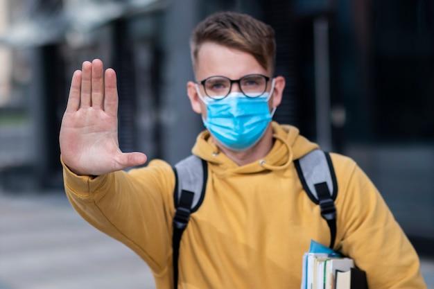 男の学生、生徒の少年、保護用の医療マスクの若い男と顔の屋外の本を持つ本、教科書は手のひら、手、兆候を停止しません。ウイルス、パンデミックコロナウイルスの概念。 covid-19