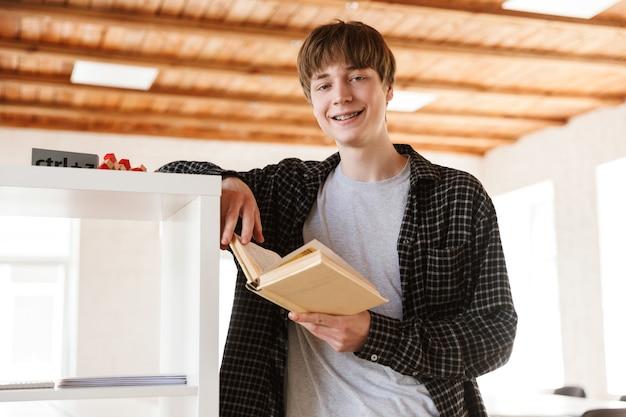 Студент парень стоял в классе в помещении, читая книгу.