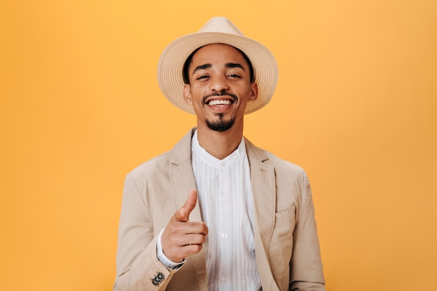 Guy in stylish hat and beige jacket smiles and shows his finger at camera
