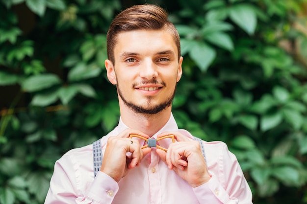 Guy in a stylish pink shirt fixes a wooden bow tie background of green leaves