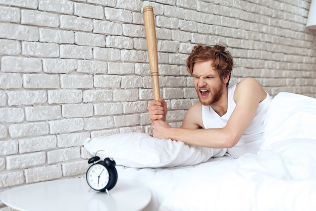 Guy swung the baseball bat on the alarm clock
