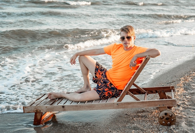 A guy in a t-shirt and shorts sits on a sun lounger by the sea