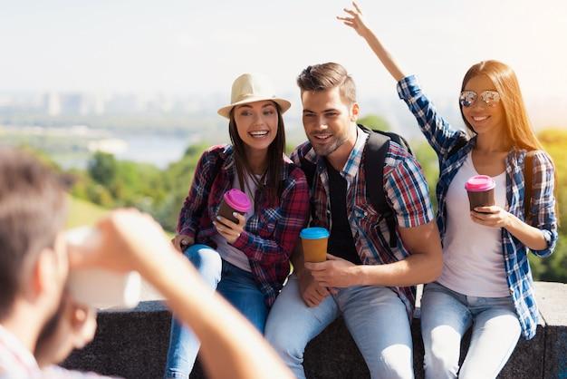 男は観光客のグループの写真を撮る。