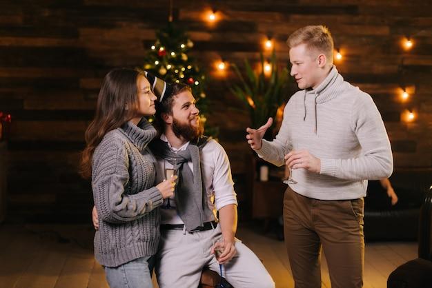 男はシャンパンのグラスを手に持ってお祝いに飾られた家で大晦日パーティーを祝うカップルに話します。背景に花輪とお祝いのイルミネーションとクリスマスツリー。