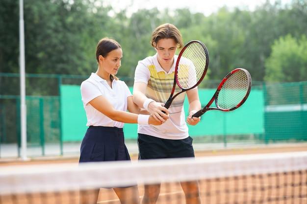 Парень учит девочку играть в теннис.