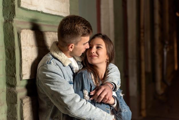男は優しい抱擁と彼のガールフレンドにキスします。夜の街で恋に幸せな若いカップル。通りのロマンチックなデート。