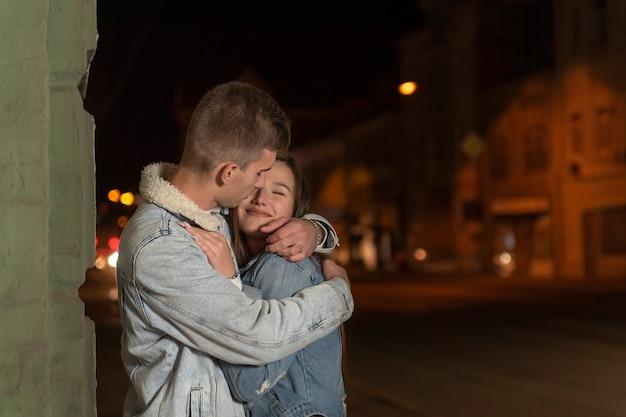 男は優しい抱擁と彼のガールフレンドにキスします。幸せな若いカップルは、夜の街の背景を抱いています。通りのロマンチックなデート。