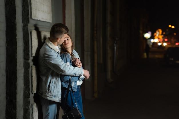 男の入札は彼のガールフレンドを抱きしめ、街での夜のデート。路上で若い愛情のあるカップル。市内の夜の日付。ロマンチックなデート