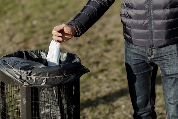 남자는 일회용 마스크를 쓰레기통에 버립니다.