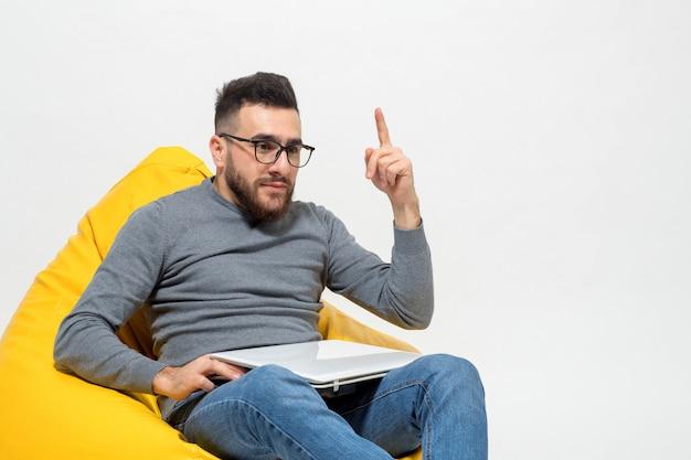 男は黄色のなよなよした椅子に座っている間にいくつかのアイデアを取りました