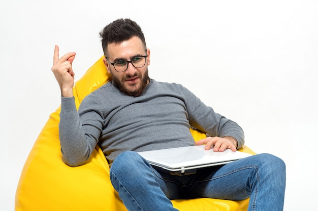 Guy took some idea while sitting on yellow pouf chair