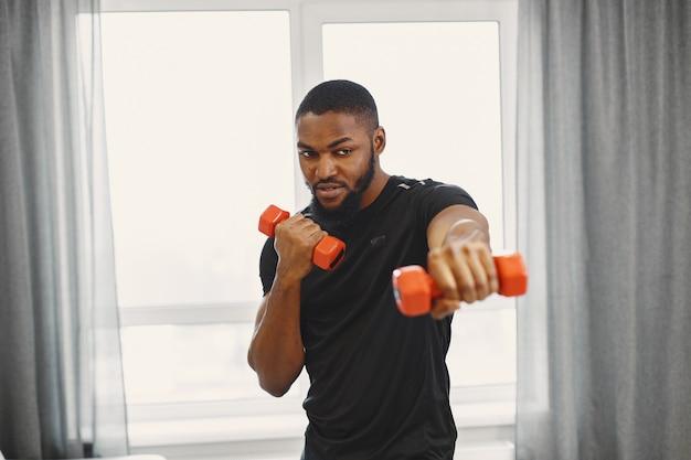 Тренировка парня дома с гантелями