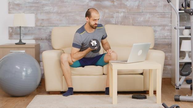 노트북에서 온라인 교육을 받은 후 아령으로 팔뚝을 훈련하는 남자.