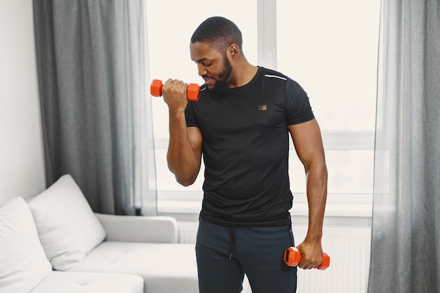 Guy training at home with dumbbells