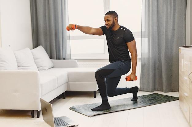 自宅でオンライントレーニングをしている男