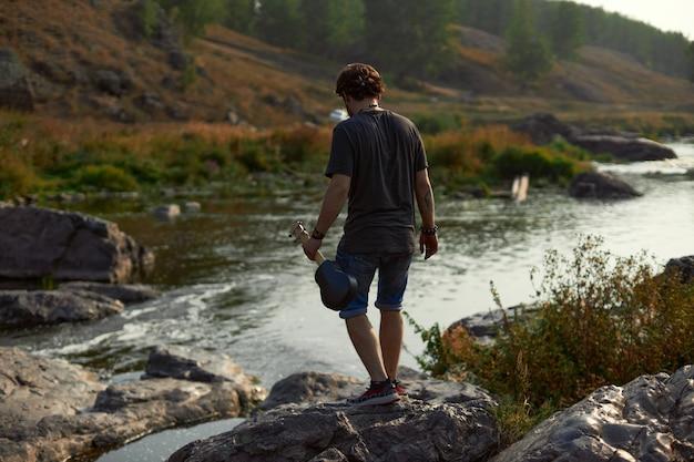 彼のハンでウクレレを持って川のそばで街の外を歩いているショートパンツとtシャツの男の旅行者...