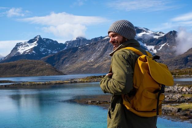 男は黄色いバックパックを持って、美しい山の風景のある絵のように美しい場所を旅します。