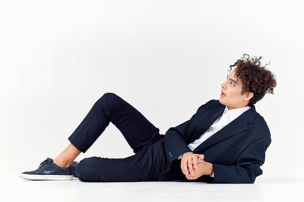Guy in trousers and a jacket lies on the floor in a bright room