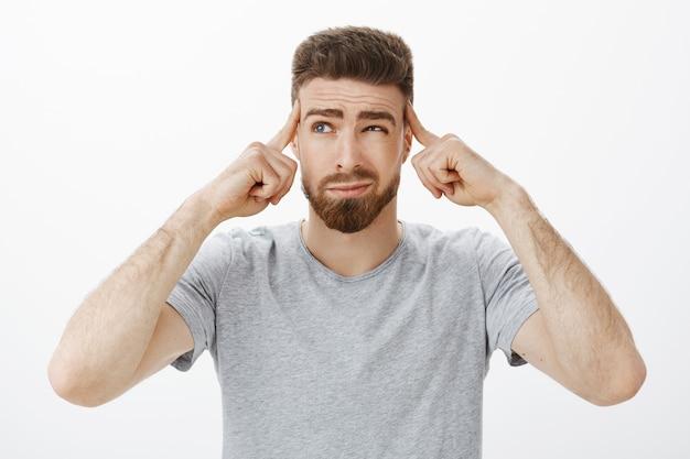 Парень пытается сосредоточиться, придумать новый план. решительный, вдумчивый красивый харизматичный мужчина с бородой и голубыми глазами, щурясь, ухмыляясь, держась пальцами за виски, сосредотачиваясь на важной игре, концентрируясь