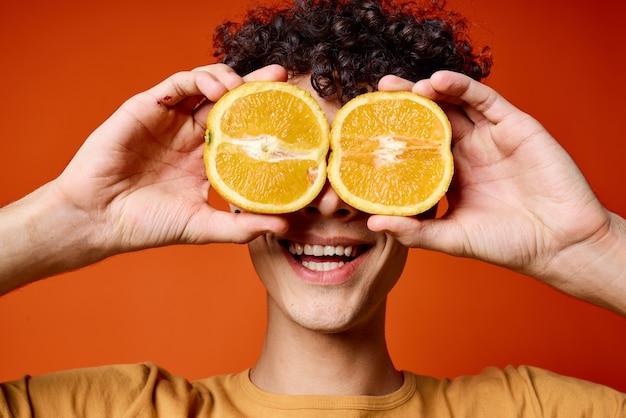 彼の手にオレンジを持った男のtシャツフルーツ健康食品