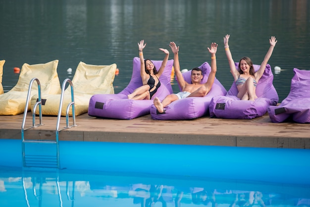 Guy and two girls sitting on cushioned lounger