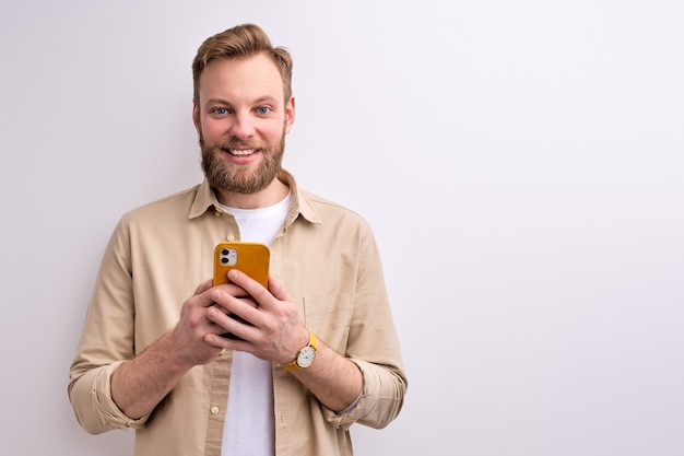 Guy typign message to someone on smartphone, having pleasant smile