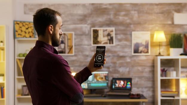 Guyは、スマートライトアプリケーションを使用して、家の電球をオンにします。スマートな未来のテクノロジー