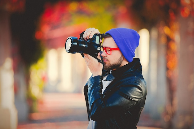 Guy using a camera for a photography in a park
