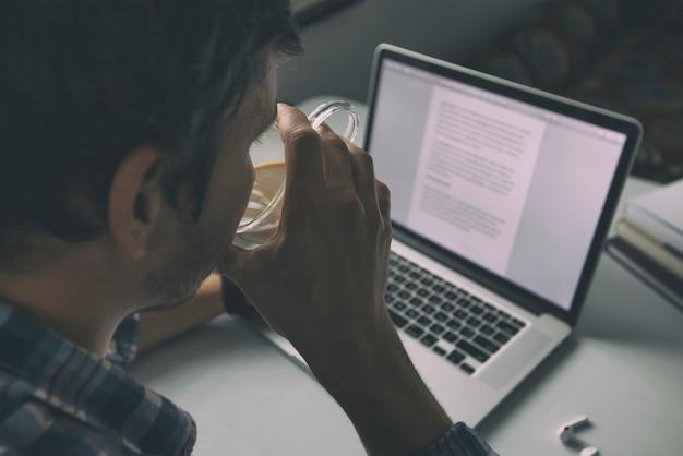 自宅でラップトップを使用してオンラインで教育した後、男は非常に疲れています