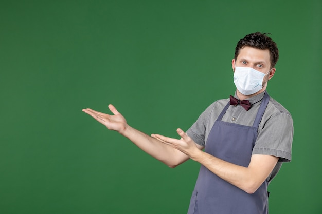 医療マスクと緑の背景の右側を上向きで制服を着た男のウェイター