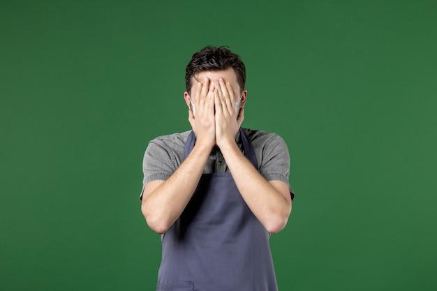 의료용 마스크를 쓴 제복을 입은 남자 웨이터는 녹색 배경에 손으로 얼굴을 감싼다