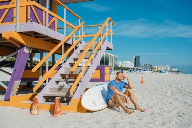 空の砂浜マイアミビーチに沿って歩く男カジュアルな服を着て座っている幸せなハンサムな男の観光客