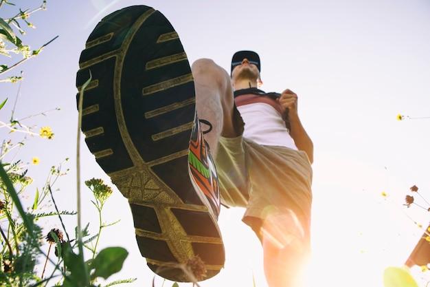 暖かい夏の朝に田舎を歩いている男。草を踏んで靴底のクローズアップビュー