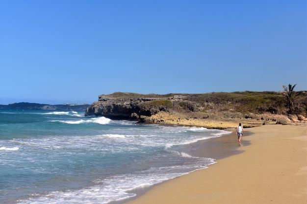 男は砂浜のビーチを歩く