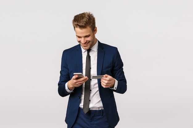 Guy want buy flowers for girlfriend, working office, holding smartphone and credit card, smiling ad enter billing details display, standing white background. businessman paying for purchase