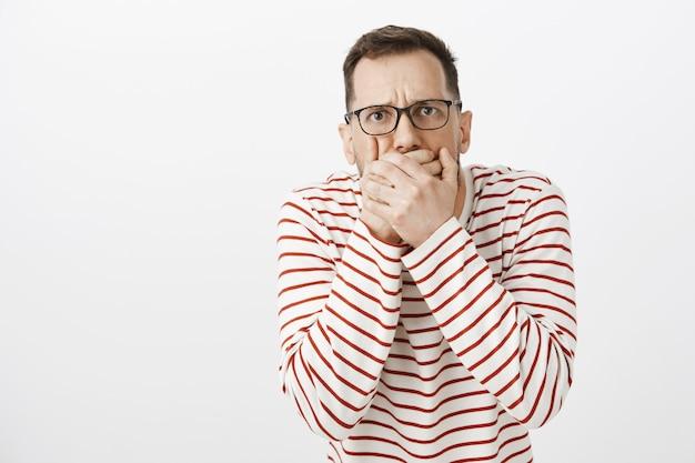 Guy want throw up tasting awful food. portrait of displeased european man in black glasses