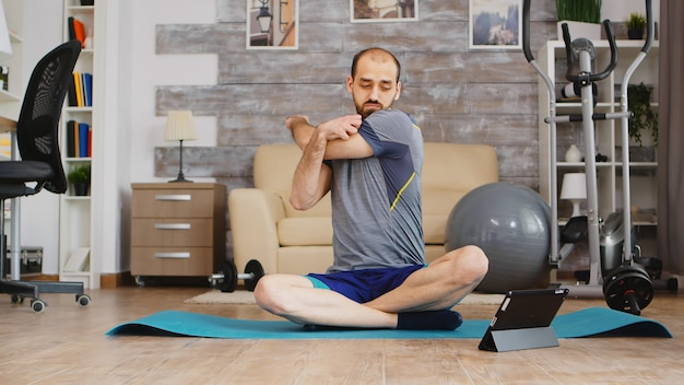 태블릿 컴퓨터에서 온라인 수업을 보면서 요가 매트에 앉아 어깨를 워밍업하는 남자.
