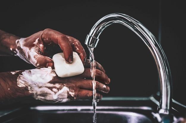 男は、黒い暗い背景の金属製の流しの上にある蛇口の下で石鹸で手を洗います。ウイルス予防。衛生的な手順。