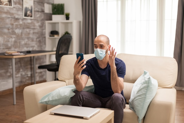 Guy waving during a video call on smartphone in time of global pandemic.