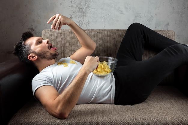 Парень в белой рубашке лежит на диване, ест чипсы и смотрит спортивный канал.